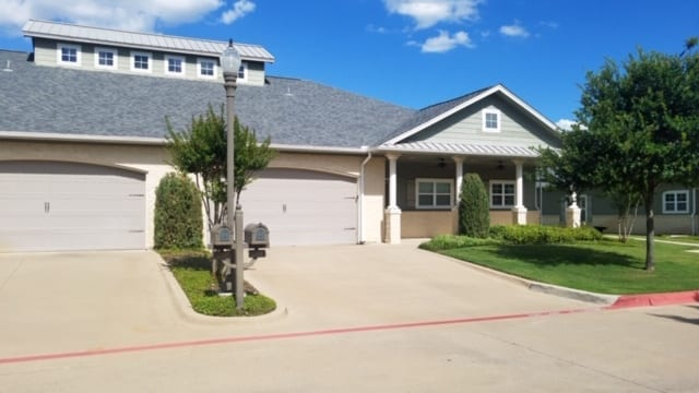 The front of a typical house with garage at the Retirement Community Parc Place in Bedford, TX