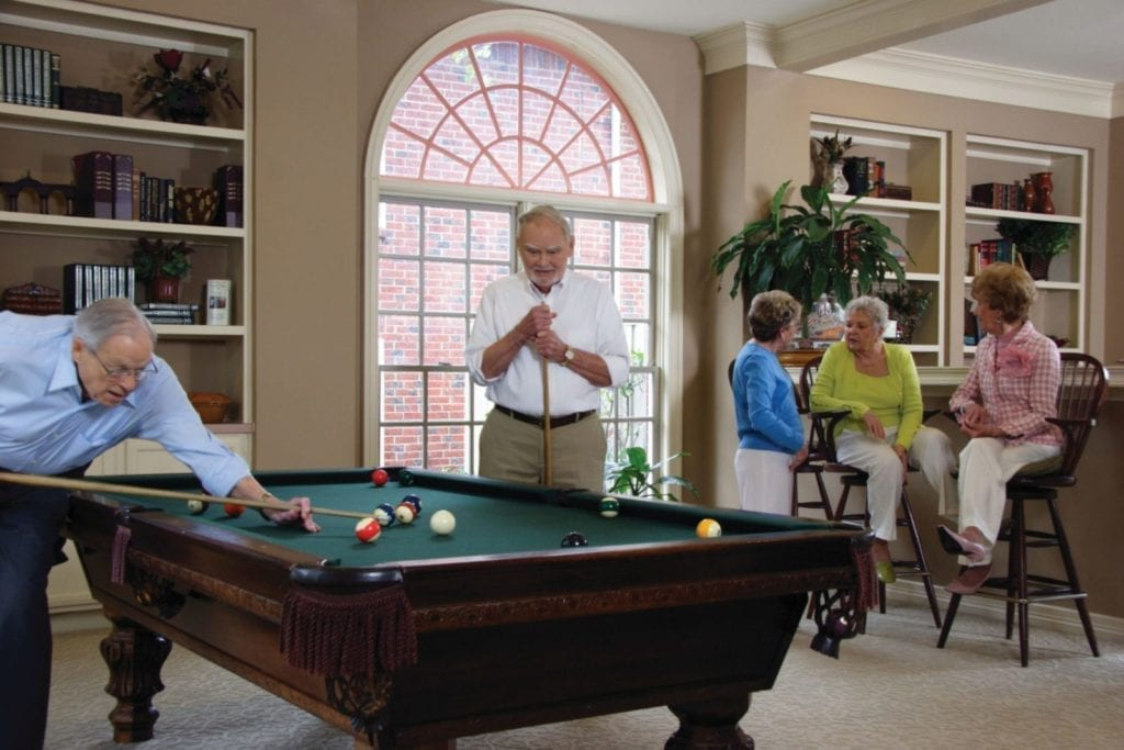 2 senior men playing pool while 3 ladies are talking in background at the recreation room of Preston Place Adult Community