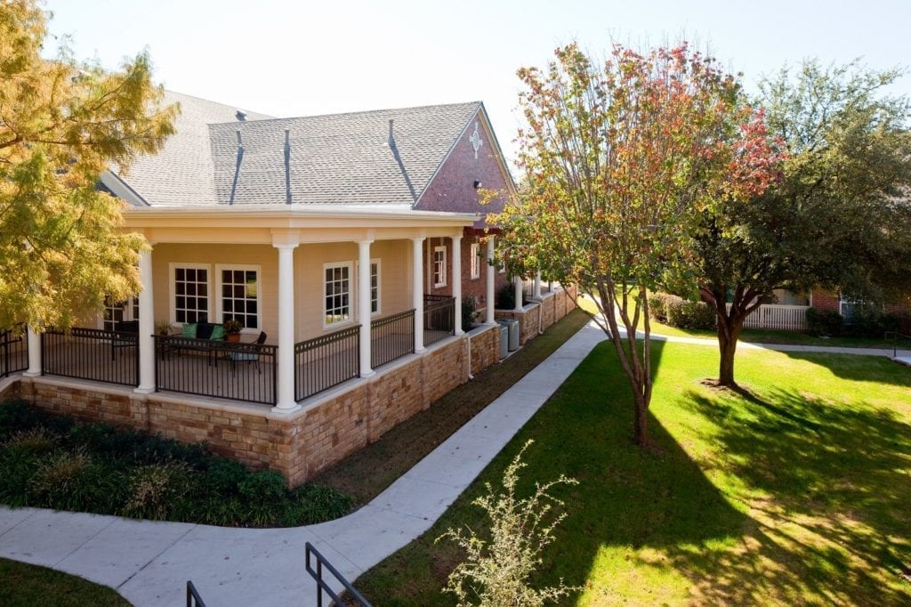 A side view of a typical house with porch at the Active Adult Community Preston Place in Plano, TX