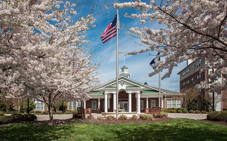 The office entrance of the Retirement Community Verena at the Reserve with cherry trees and USA flag waving in the air