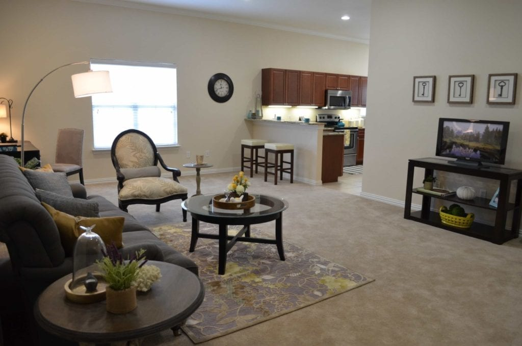 Typical apartment living room and kitchen at the Retirement Community Parc Place in Bedford, TX