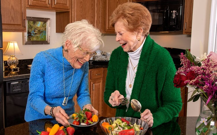 2 senior ladies cooking and laughing at their kitchen at the Retirement Community Verena at the Reserve in Williamsburg, VA