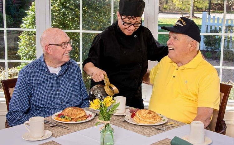 A waitress serving coffee to 2 senior residents of the Retirement Community Verena at the Reserve in Williamsburg, VA