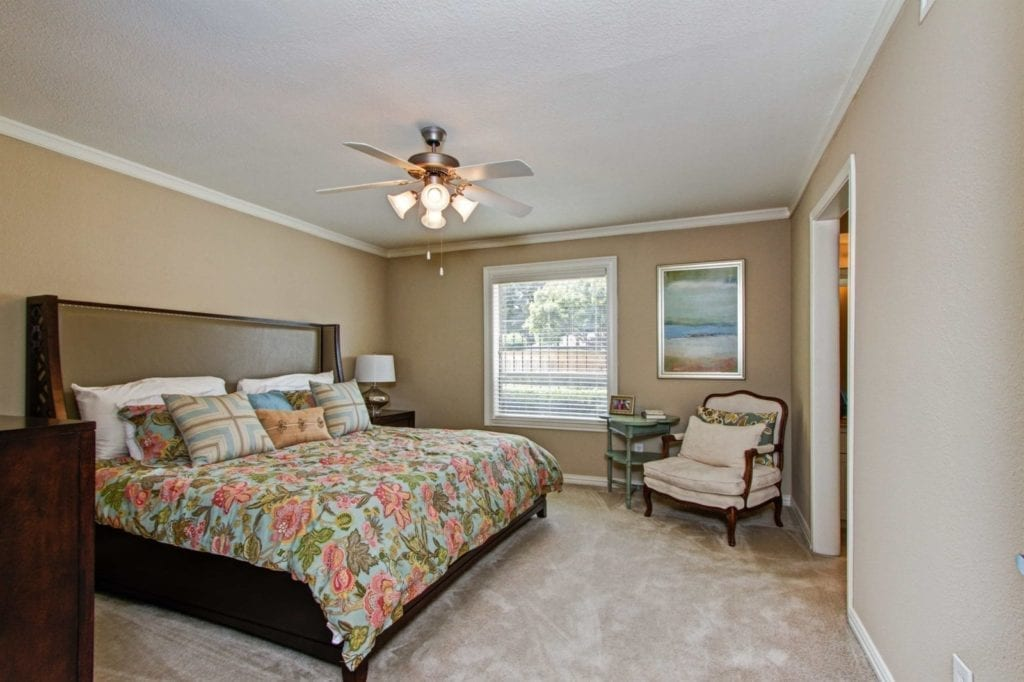 Typical apartment bedroom with king size bed at the Active Adult Community Meadowstone Place in Dallas, TX