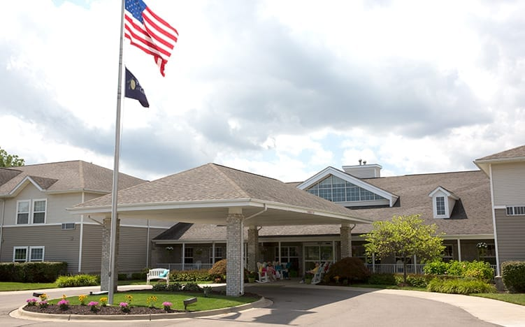 The entrance of Pine Ridge of Garfield Senior Living Apartments in Clinton Township, MI with USA flag waving in the air