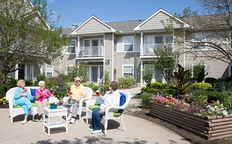 Senior Residents Hanging Out in the Backyard of Pine Ridge of Garfield Senior Living Apartments in Clinton Township, MI