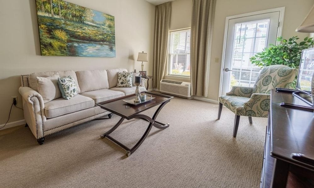 A beautiful and bright apartment living room of the Senior Living Community Arbour Square of Harleysville, PA