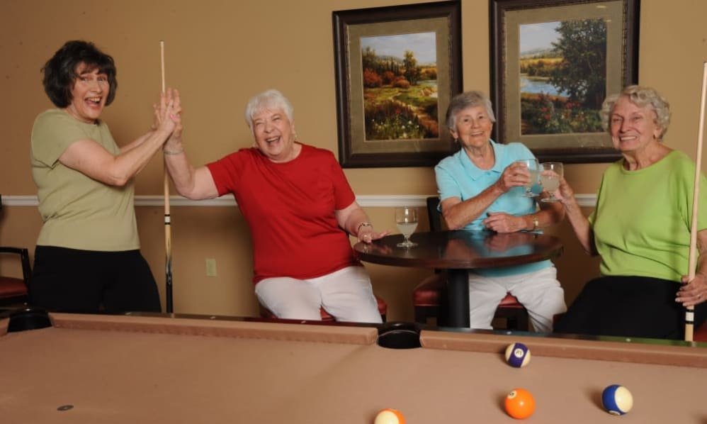 A group of senior ladies drinking and playing pool at the Senior Living Community Arbour Square of Harleysville, PA