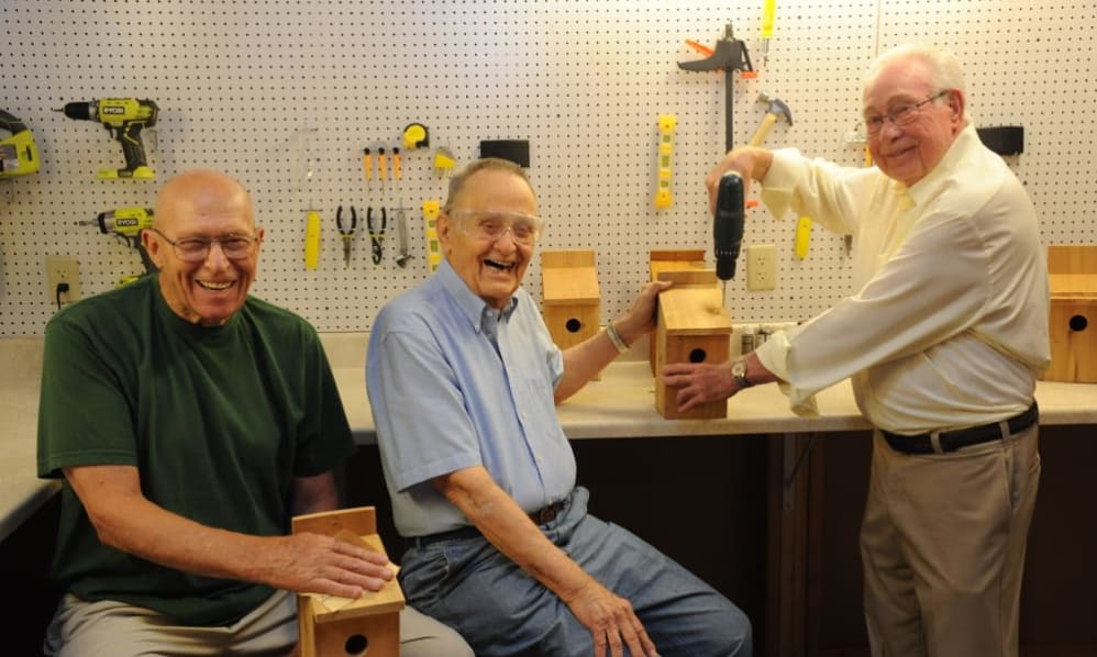 A group of senior men working with wood at the art studio of the Senior Living Community Arbour Square of Harleysville, PA