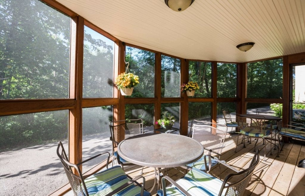 Sunroom with a seating set and flowers hanging on the wall at Senior Living Pine Ridge Villas of Shelby