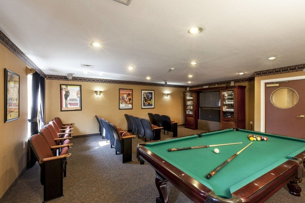 Entertainment room with movie set and pool table at Pine Ridge of the Plumbrook Senior Living in Sterling Heights, MI