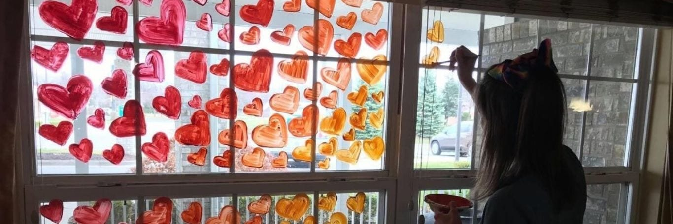 A Woman Painting Colorful Hearts on the Window of Pine Ridge of Garfield Senior Living House