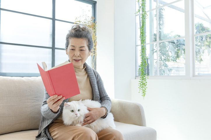 A woman sitting on the couch and reading with her cat on her lap